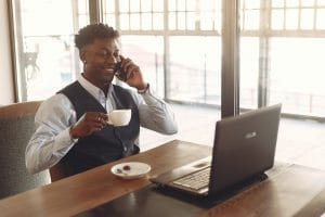 ethnic man drinking coffee working in coworking space