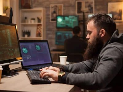 Adult hacker typing a virus on computer to break firewall